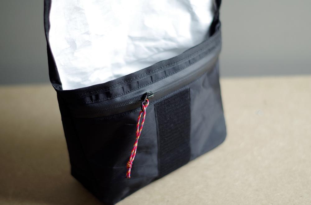 En position ouverte, la pochette est dotée d'une poche zippée. La fermeture éclaire est imperméable.