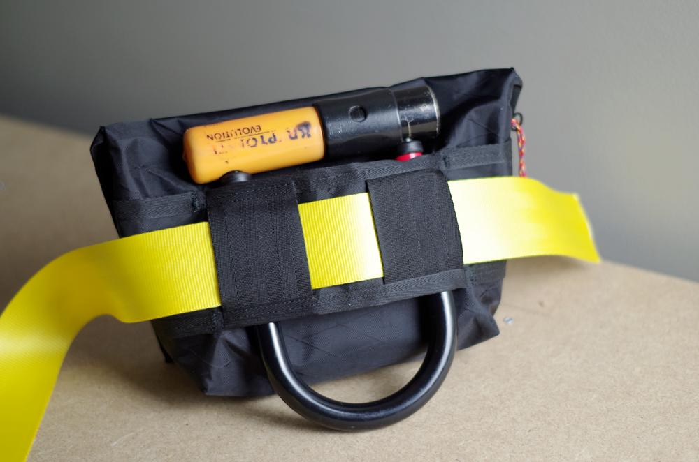 A l'arrière, les passants peuvent accueillir des ceintures jusqu'à 60mm. La sangle jaune fait 50mm. On garde toujours le porte U Kryptonite. De chaques côtés, les espaces permette de passer un stylo ou une lampe torche.